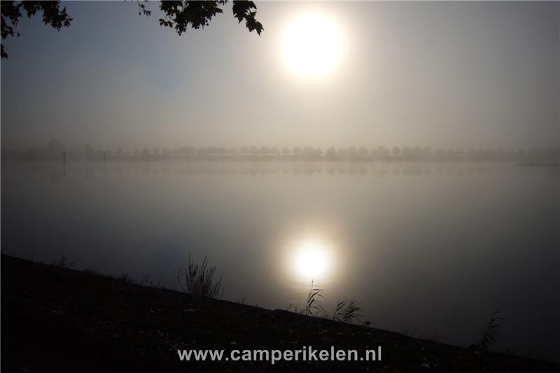 Zonopkomst boven de rivier in de mist